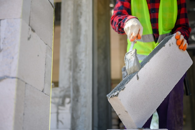 Bauarbeiter wir verputzen den klebemörtel, der mit leichtbeton gebaut wird. techniken zum auftragen von klebemörtel auf einer baustelle.