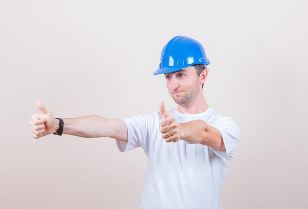 Bauarbeiter zeigt doppelte daumen in t-shirt, helm und sieht jovial aus