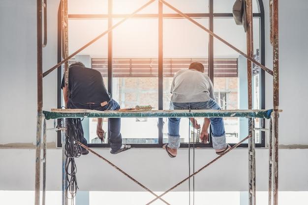 Bauarbeiter zwei, der sätze metall- und plastikfenster in hotel installiert