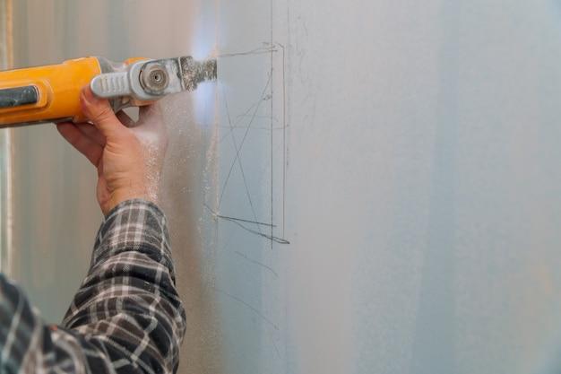 Bauarbeiterausschnittgipskartonplatte unter verwendung des elektrischen schneiderwinkelschleifers