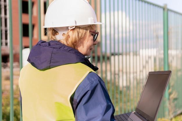 Bauarbeiterfrau auf der baustelle in grüner weste und helm mit laptop