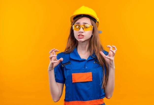 Bauarbeiterin der jungen frau in der bauuniform und im schutzhelm, die hass auf jemanden fühlen, der in aggressivem ausdruck gestikuliert, der über orange wand steht