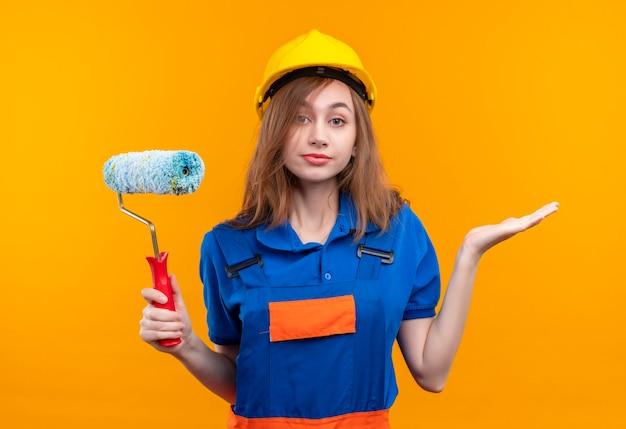 Bauarbeiterin der jungen frau in der bauuniform und im sicherheitshelm, der farbroller hält, der verwirrtes achselzucken steht, das über orange wand steht