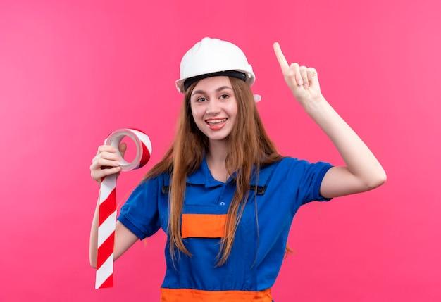 Bauarbeiterin der jungen frau in der bauuniform und im sicherheitshelm, der klebeband hält zeigefinger nach oben lächelnd mit großer idee über rosa wand steht