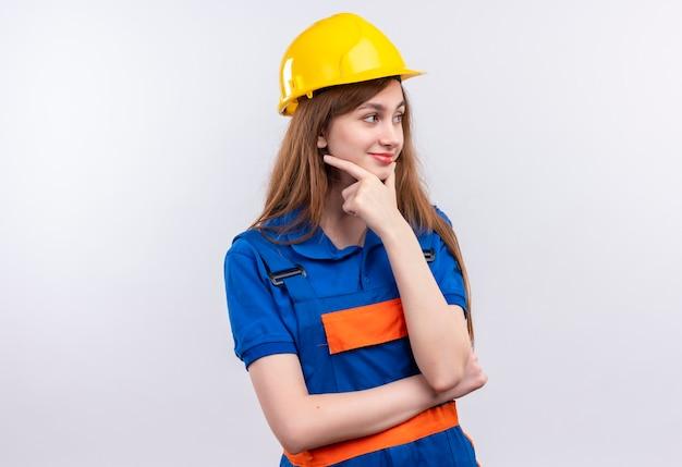 Bauarbeiterin der jungen frau in der bauuniform und im sicherheitshelm, die beiseite schauen mit hand auf kinn mit nachdenklichem ausdruck, der über weiße wand denkt