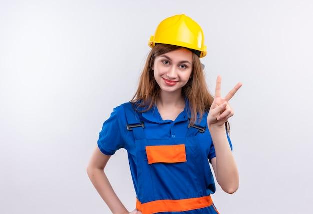 Bauarbeiterin der jungen frau in der bauuniform und im sicherheitshelm, die das siegeszeichen lächelnd freundlich stehend über weißer wand zeigen