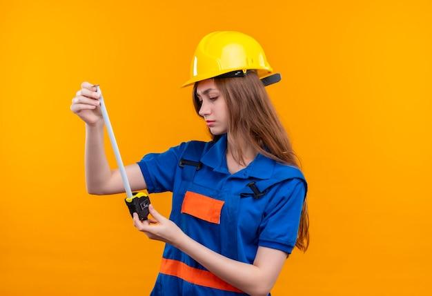 Bauarbeiterin der jungen frau in der bauuniform und im sicherheitshelm, die maßband betrachten, das es mit ernstem gesicht betrachtet, das über orange wand steht