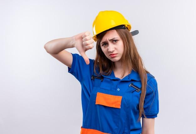Bauarbeiterin der jungen frau in der bauuniform und im sicherheitshelm, die unzufrieden aussehen, zeigt daumen nach unten stehend über weißer wand
