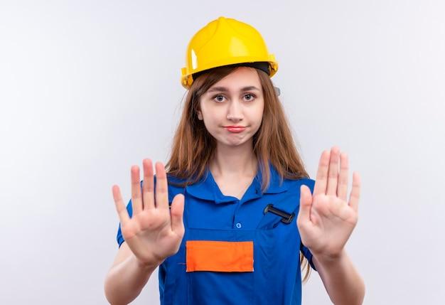Bauarbeiterin der jungen frau in der bauuniform und im sicherheitshelm, die unzufrieden stehen, die mit offenen händen stehen und stoppschild über weißer wand machen
