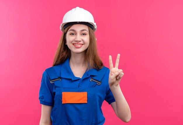 Bauarbeiterin der jungen frau in der bauuniform und im sicherheitshelm lächelnd, die fröhlich siegeszeichen auf nummer zwei über rosa wand stehend zeigen