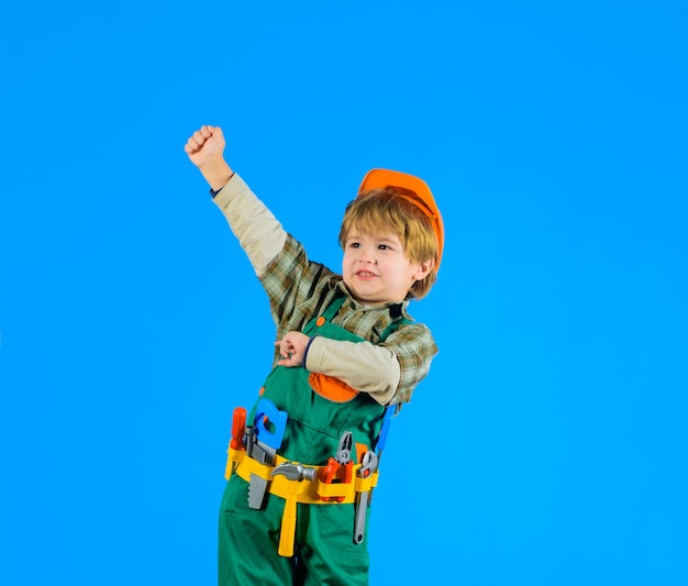 Bauarbeiterjunge kleiner junge in baumeisteruniform mit spielzeugwerkzeugkind, das mit reparaturwerkzeugbau spielt