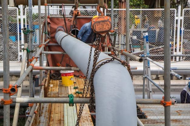 Bauarbeiterkettenzug, der rohrventile in der öl- und gaspipelineindustrie auf der baustelle installiert