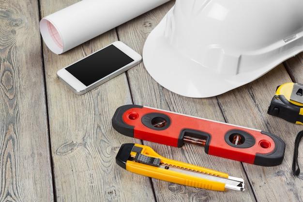Bauarbeiterzubehör und -instrumente auf holztisch
