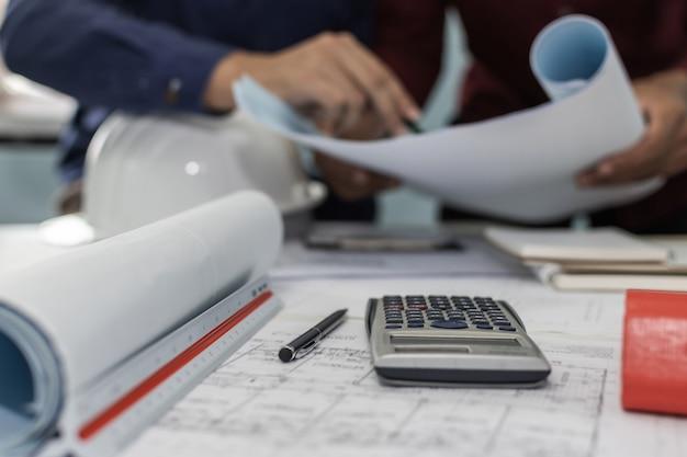 Bauarbeitswerkzeug, taschenrechner, blaupause und schutzhelm auf schreibtisch des architektenarbeitsplatzes mit architekt im bürozentrum des besprechungsraums auf baustelle, bau-, ingenieurwerkzeugkonzept