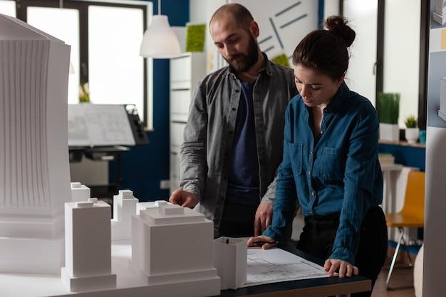 Bauarchitektenteam, das im schreibtischbüro an blaupause arbeitet