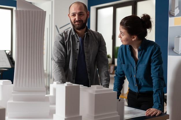Bauarchitektenteam, das im schreibtischbüro an blaupausenlayout arbeitet, kaukasische kollegen stehen...