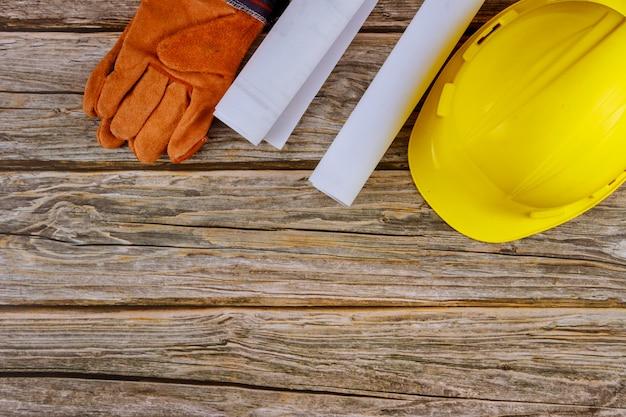 Baubüro, das mit blaupausen im satz der arbeitsschutzkleidung in den gelben schutzhandschuhen des schutzhelms arbeitet