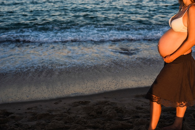 Bauch der schwangeren frau zu fuß am strand, meer im hintergrund.
