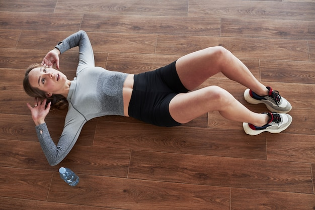 Bauchmuskeln machen sportliche junge frau haben fitness-tag im fitnessstudio zur morgenzeit
