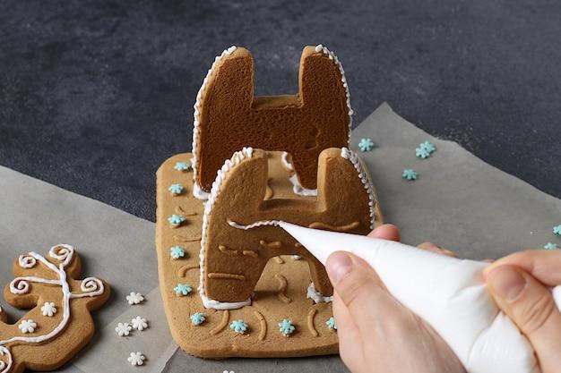 Bauen sie zu hause lebkuchen in hirschform. schritt für schritt. mädchen bemalt lebkuchen mit zuckerguss