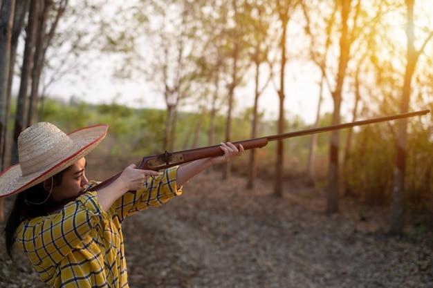 Bauer asia frau mit hut am schießstand schuss aus einer vorderlader vintage-pistole