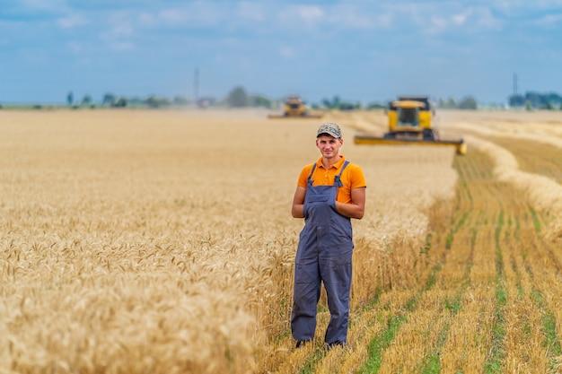 Bauer im weizenfeld mit arbeitsmähdrescher im hintergrund. blauer himmel oben.