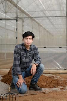 Bauer in kariertem hemd und jeans sitzt in der nähe eines erdhaufens zum pflanzen im gewächshaus.