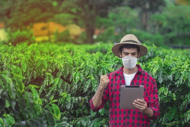 Bauer mit covid-pandemie-maske und tablet auf der plantagen-feldfarm