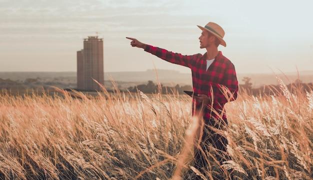 Bauer mit hut in der farmplantage, die auf sonnenuntergang zeigt.
