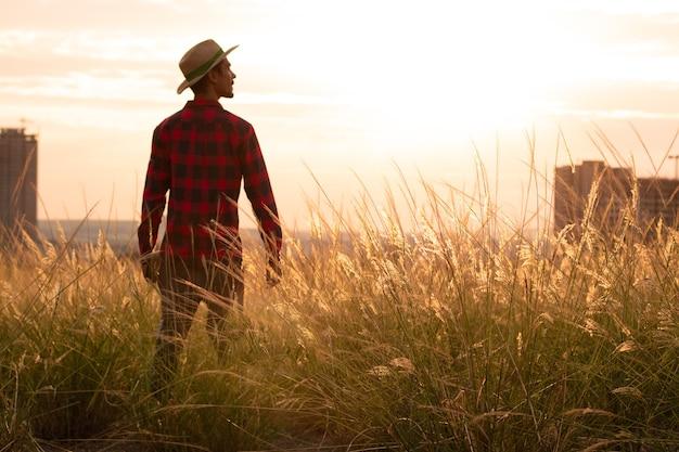Bauer mit hut in farm plantage bei sonnenuntergang.
