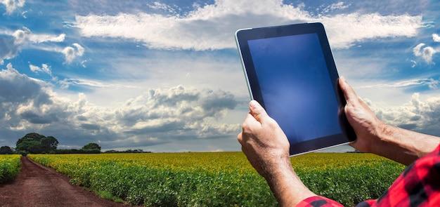 Bauer mit tablet-computer auf der landschaft der sojabohnenplantage bei sonnenuntergang