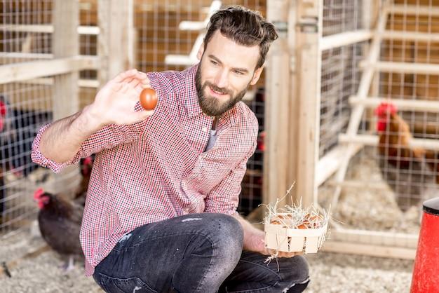 Bauer sammelt eier im hühnerstall aus holz mit hühnern