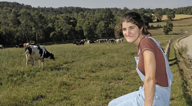 Bauer sitzt auf einem zaun und hinter ihrer kuhherde