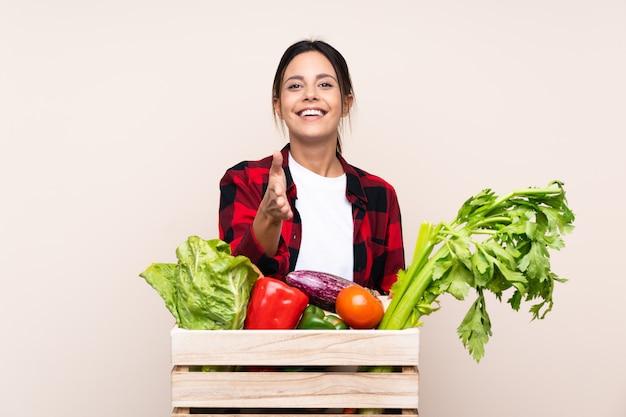 Bauernfrau, die frisches gemüse in einem hölzernen korb händeschütteln nach vielem hält