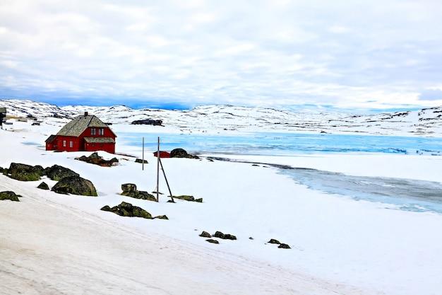 Bauernhaus am ufer eines zugefrorenen sees