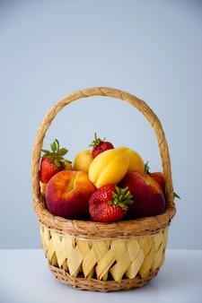 Bauernhofkorb gefüllt mit verschiedenen bunten früchten und beeren auf weißem tisch: pfirsiche, erdbeere und aprikose