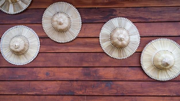 Bauernhut aus palmblättern zeigt dekoration auf holzbrettwand.
