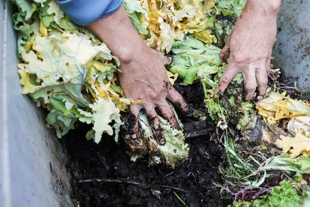Bauernmann, der kompost mit würmern hält