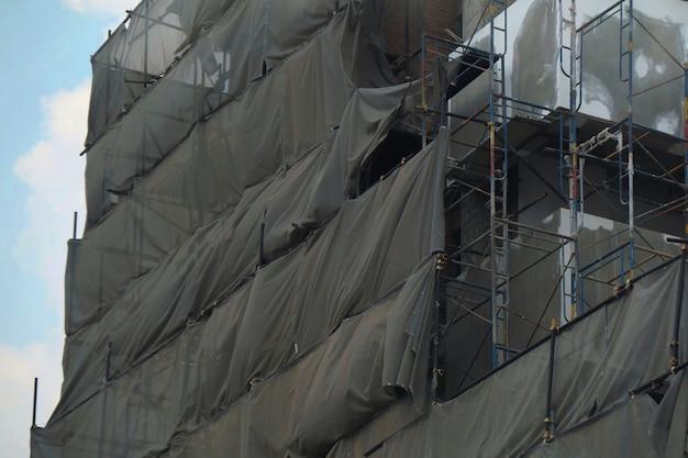 Baugerüst mit grauer abdeckung am gebäude mit blauem himmel industriekonzept