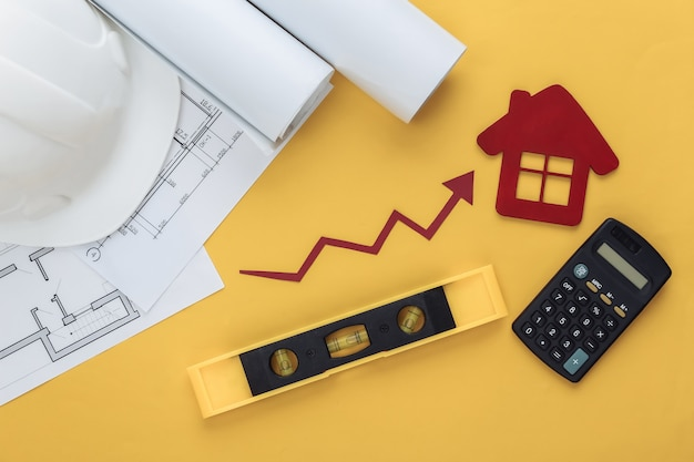 Bauhelm, blaupause, haus, ingenieurbaubedarf und wachstumspfeil, der auf gelb nach oben neigt