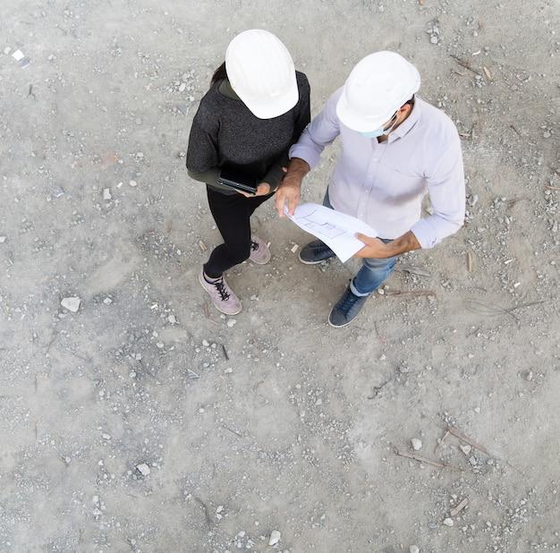 Bauherr und ingenieur in der schützenden gesichtsmaske arbeiten auf der baustelle mit blick auf pläne draufsicht