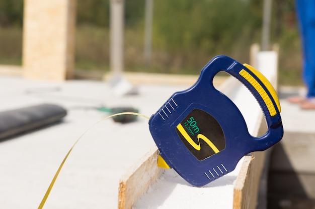 Bauherren blaues einziehbares kunststoff-maßband, das auf einer isolierten wandplatte auf einer baustelle ruht
