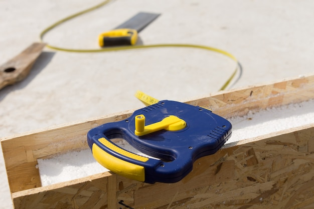 Bauherren-maßband, das auf einer isolierten holzwandplatte auf einer baustelle liegt, nahaufnahme