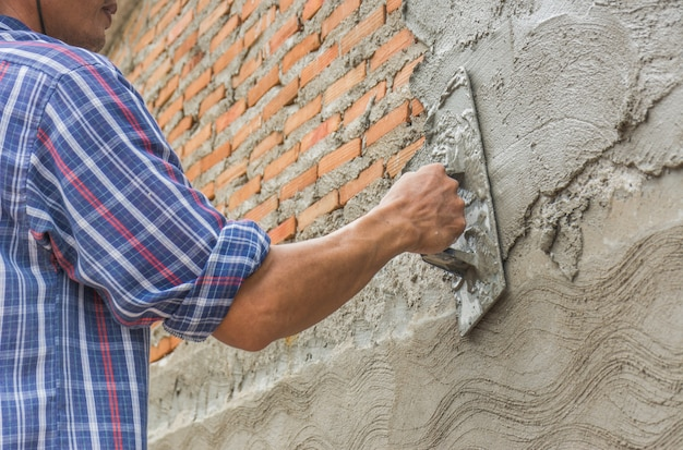Bauherren verputzen die wände des hauses mit ordentlichkeit.
