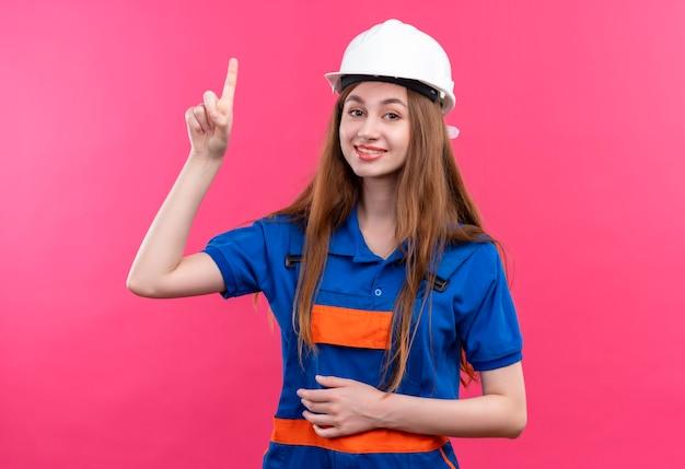Bauherrin der jungen frau in der bauuniform und im sicherheitshelm, der finger oben zeigt, der große idee hat, über rosa wand stehend zu lächeln