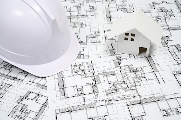 Bauindustriekonzept mit einem schutzhelm auf architekturzeichnung
