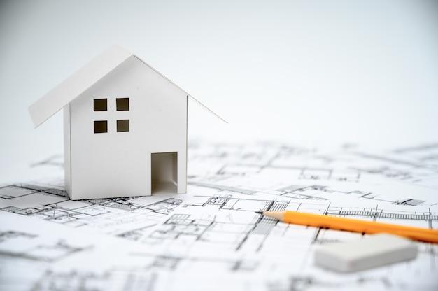 Bauindustriekonzept mit stiften und hausmodellen auf architekturzeichnungen