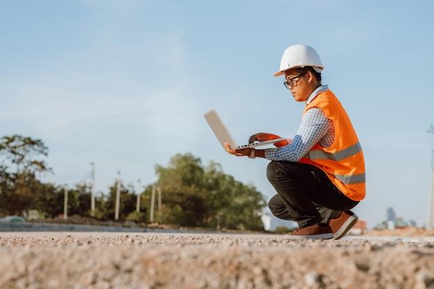 Bauingenieur auf der baustelle unter verwendung der computer-laptop-überprüfungsarbeit. management auf der baustelle.