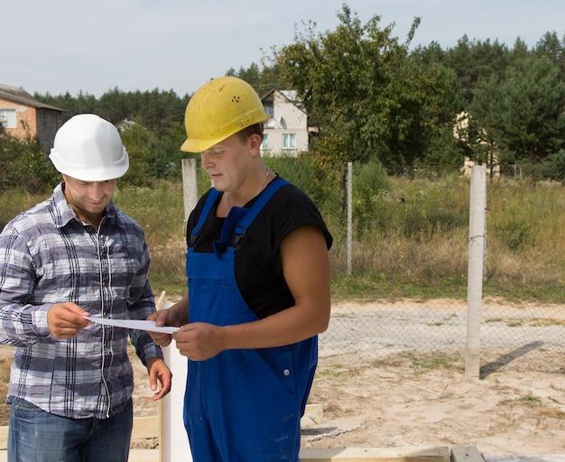 Bauingenieur aus dem mittelalter im gespräch mit bauarbeiter über die projektpläne auf der baustelle.