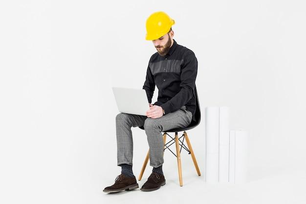 Bauingenieur, der gelben hardhat unter verwendung des laptops trägt